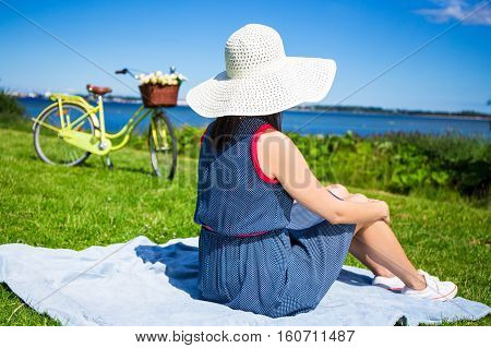 Back View Of Woman In Hat Sitting On The Sea Coast With Vintage Bicycle