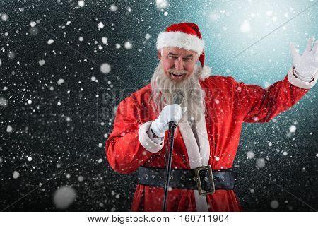 Portrait of Santa Claus singing Christmas songs against snow