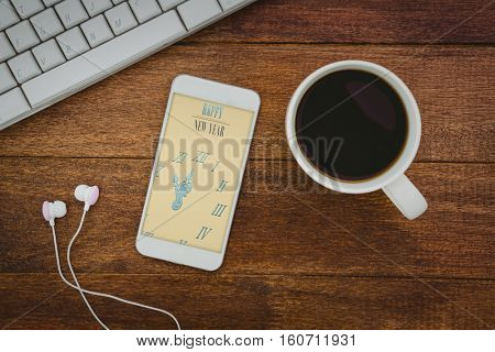Digital image of new year message and clock against view of a mug of coffee and a smartphone
