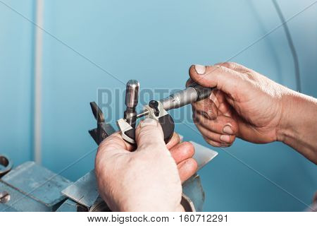 mechanical technician worker hands measuring detail tool after processing at workshop with sliding caliper at manufacturing