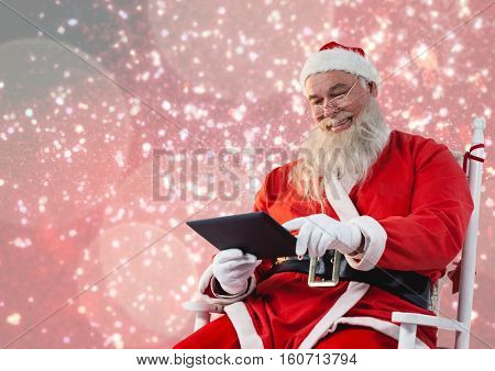 Santa claus sitting on chair and using a digital tablet