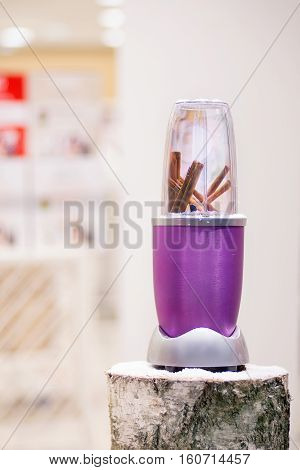 Close view of a blender with cinnamon sticks on a snowy log Christmas gift.