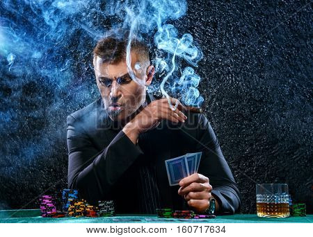 Rich gambler man with the cards and chips in casino. Gambling, playing cards and roulette.