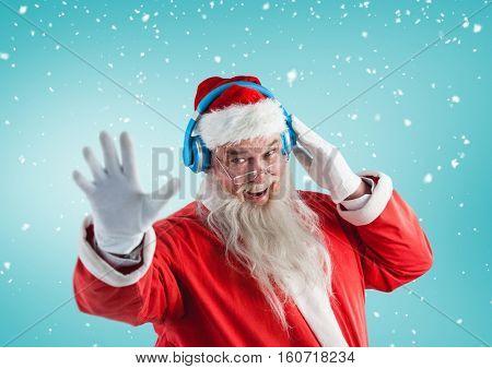 Santa gesturing while listening music on headphones against digitally generated blue background