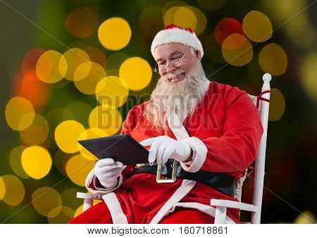 Santa sitting on chair and using digital tablet against bokeh lights background