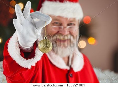 Portrait of santa claus holding golden christmas bauble