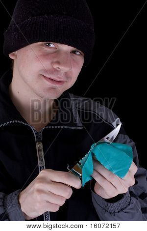 Young man with knife on black background