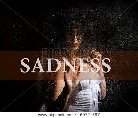 sadness written on virtual screen. hand of young woman melancholy and sad at the window in the rain