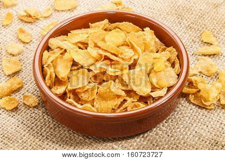 cornflakes in a brown clay bowl on jute