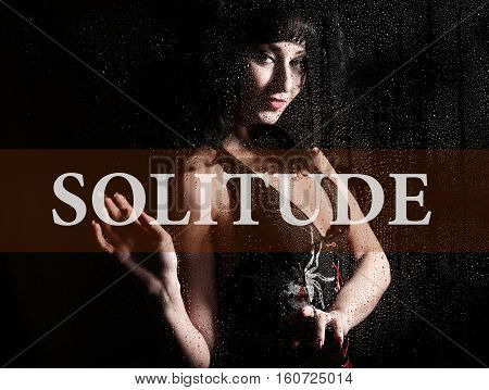 solitude written on virtual screen. hand of young woman melancholy and sad at the window in the rain