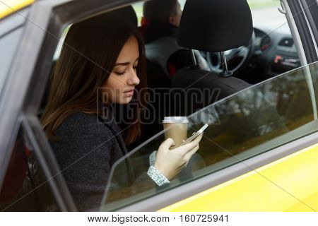 Young woman with coffee and phone in hand coming out of taxi