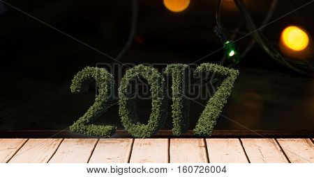 2017 in grass on wooden plank against a composite image 3D of christmas lights at night