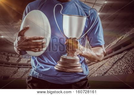 Mid section of sportsman holding trophy and rugby ball against rugby stadium 3D