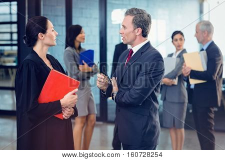Side view of lawyer interacting with businessman while standing in office