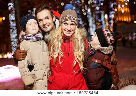 Cheerful mother with kids in Christmas night outdoors