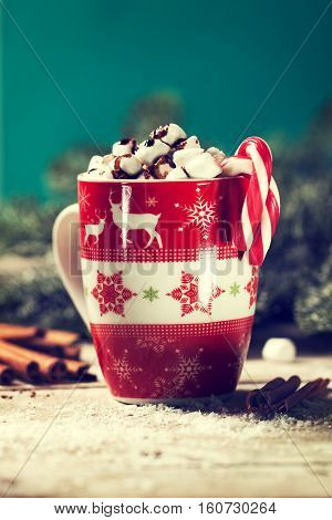 Homemade sweet tasty Hot Chocolate with Marshmallow and Candy Canes in red Cup on a Christmas Background. Vintage toning closeup