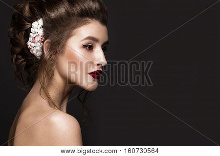 Beautiful girl with classic make-up, wedding hairstyle, bright lips. The beauty of the face. Photos shot in studio