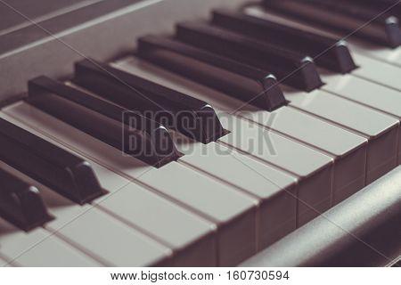 Piano keyboard black and white keys close-up musical instrument retro toning selective focus
