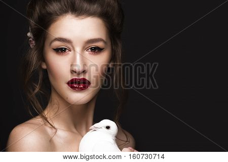 Beautiful girl with classic make-up, wedding hairstyle, bright lips and a dove in her hands. The beauty of the face. Photos shot in studio