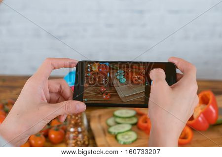 Young woman cooking and taking photo of vegetables by smartphone. Picture of food on screen.
