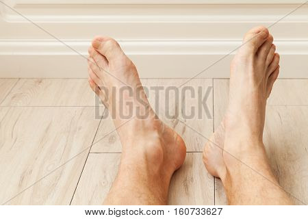 Relaxing Male Feet On Wooden Floor