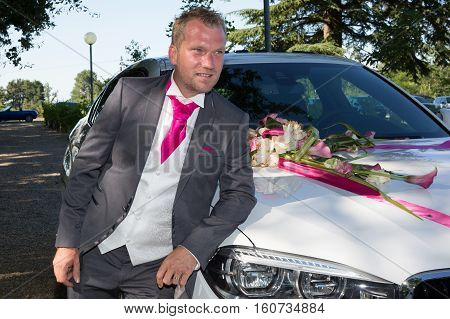 The Groom In Front Of White Luxury Car In Wedding