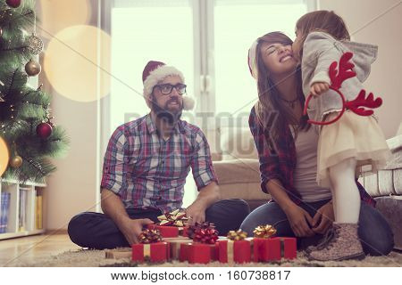 Young family on Christmas morning exchanging presents and enjoying their time together. Daughter kissing mother. Focus on the mother