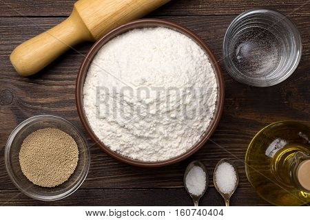 Ingredients for homemade pizza dough on dark rustic background. Top view.