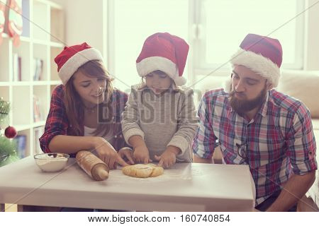 Beautiful young family having fun while baking a Christmas cookies. Focus on the baby girl