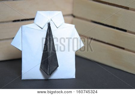 Abstract concept of white collar worker with origami suit and black tie. Wooden background