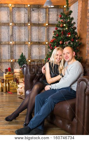 Couple resting on sofa in home decorated for christmas