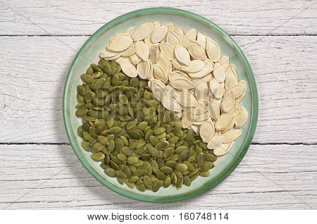 Pumpkin seeds peeled and in the shell in plate on white wooden table top view