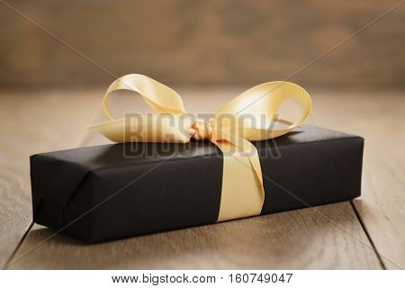 handmade gift black paper box with yellow ribbon bow on wood table, closeup photo