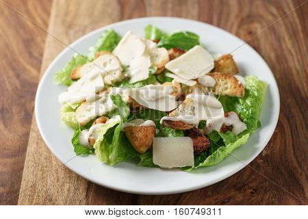 caesar salad with chicken on old wooden table, shallow focus