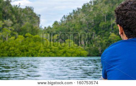 Traveler looking into Mangrove Jungle near Warikaf Homestay, Kabui Bay and Passage. Gam Island, West Papuan, Raja Ampat, Indonesia.