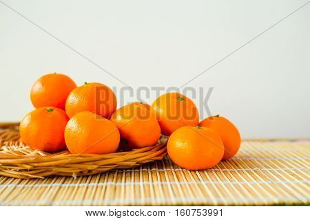 Many raw orange mandarins lying at plate on bamboo mat. Healthy food concept. Objects.