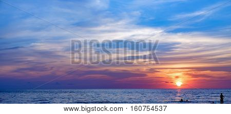 Panoramic view of the sea at colorful sunset, Koh Chang, Thailand. Silhouette man and child playing ball on the water
