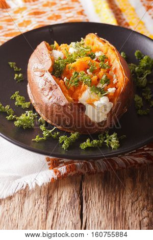 Orange Sweet Potatoes Baked With Cream Cheese, Spices And Herb Close-up On A Black Plate. Vertical