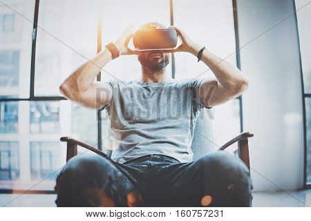 Attractive bearded man enjoyingvirtual reality glasses in modern interior design coworking studio.Home play concept.Smartphone use with VR goggles headset. Front view, flare effect, blurred background