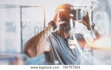 Concept of digital screen, connection and interfaces.Young bearded man enjoyingvirtual reality glasses in modern design home studio.Smartphone use with VR goggles headset.Horizontal, flare, blurred