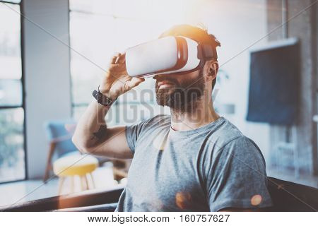 Attractive bearded man wearing virtual reality glasses in modern interior coworking studio.Hipster using smartphone with VR goggles headset.Horizontal, film effect, flare, blurred background