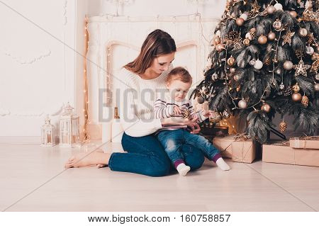 Beautiful mother sitting with baby girl under 1 year old on floor with Christmas tree in room. Togetherness. Celebration. 20s.