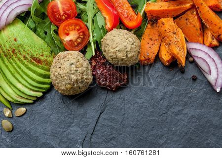 Vegan food frame: avocado sweet potato lentil cutlets tomatoes arugula onions on black stone background with a copy space in the center