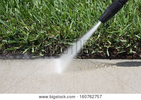 Image of pressure cleaning being done to a sidewalk
