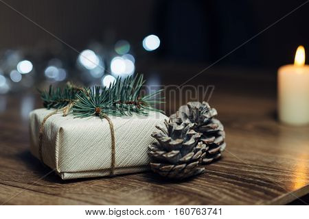 Burning candle on a table with Christmas decorations pine cones and a box on the background of garlands