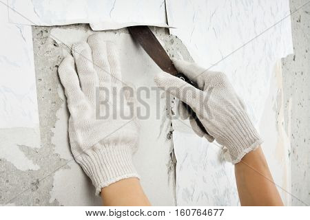 hand in gloves scraping off old wallpaper with spatula