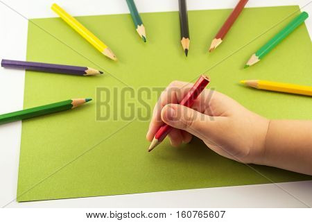 Kids hand holding a red pencil on green background