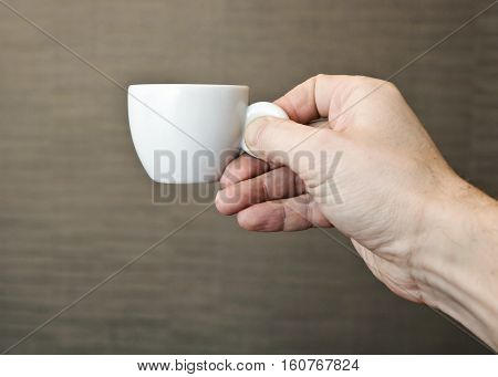 Male hand holding small espresso coffee cup