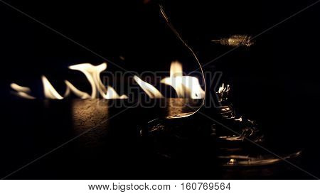 stemmed glass in front of fire in the dark