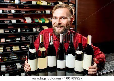 Portrait of a handsome sommelier hugging wine bottles at the luxury supermarket or restaurant